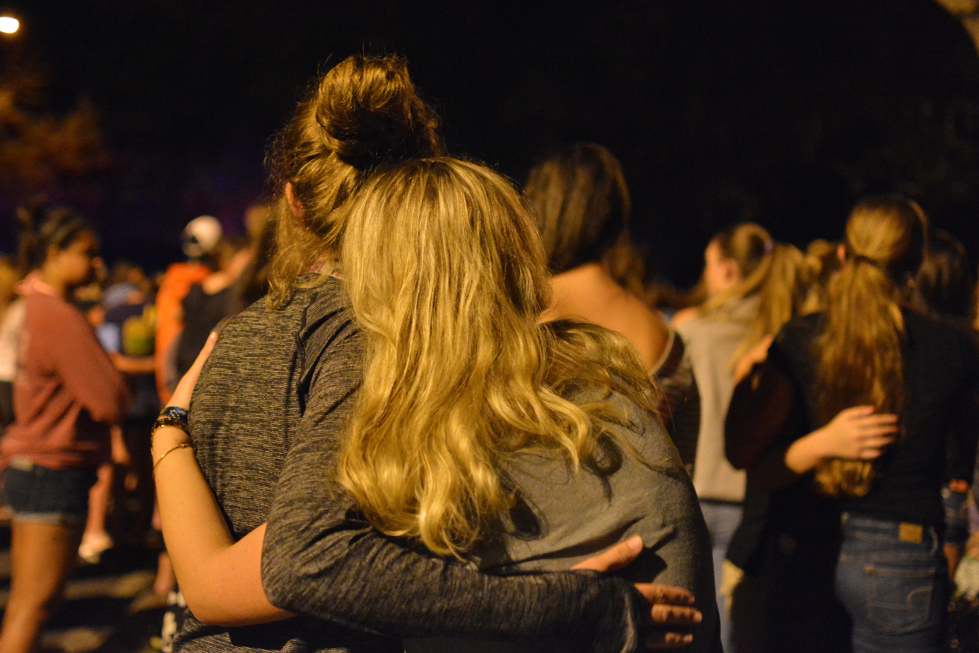 Lucy Milbourn and Ali Alger share an embrace as they stand at the candlelight vigil.