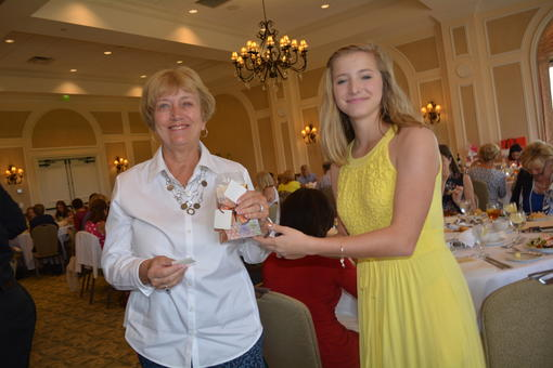 Janet Hough won an Alex and Ani brand lobster charm bracelet from the silent auction. Carli Kasten, who suffers from Cystic Fibrosis, hands out the prizes.