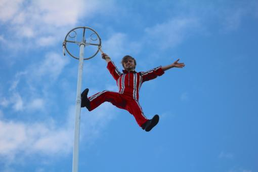 Nock Productions' Andrew Nock sways high in the sky as World Rowing Championship attendees enter the park for the opening ceremony.