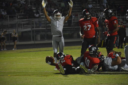 "Senior wideout Craivon Koonce (1) signals ""touchdown"" as Deshaun Fenwick extends the ball over the goal line."