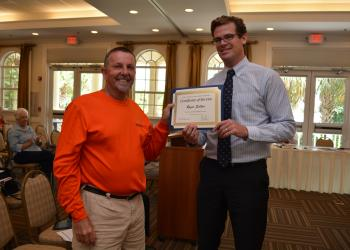 Roger Sutton receives his 10-year service award from Ryan Heise, director of operations of Lakewood Ranch Town Hall.