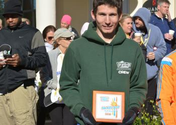 Overall champion Michael Lamb of Bradenton poses with his plaque. Lamb, a University of South Florida student, set a personal best at 1:14.32.