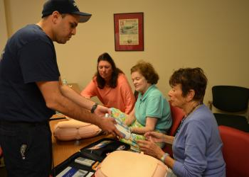 Firefighter/paramedic Jose Rivera  teaches Bayport residents Chris Lake, Arlene Scarlett and Sue Rosen how to use an automatic external defibrillator Feb. 3 at the north fire station.