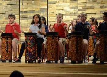 Third and fourth-graders beat the drum to the music.