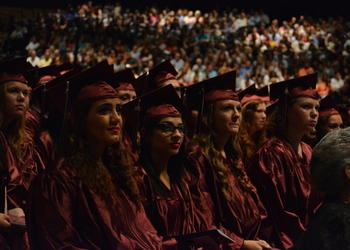 Graduates listen to commencement speakers and watch a video of photographs of the Class of 2016.