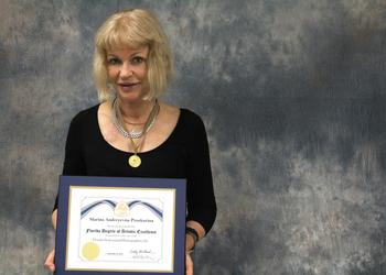 Marina Proskurina, teacher of digital design at Manatee Technical College, wears her medal and holds the unique degree she recently earned.