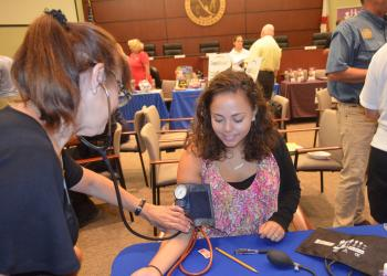 Diane Proios checks Town Planner Maika Arnold's blood pressure at the Longboat Key health fair May 21. Photo by Kristen Herhold
