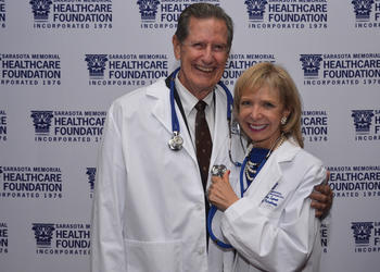Chairman of the Sarasota Memorial Healthcare Foundation Board of Trustees Jim Syprett with his wife, Charlie Ann Syprett, after receiving their Doctors of Philanthropy lab coats