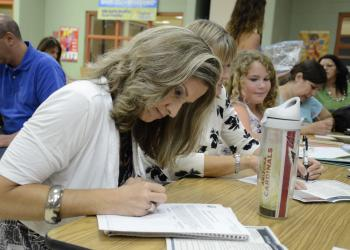 Susan Myers, a McNeal parent, writes down notes about each candidate.