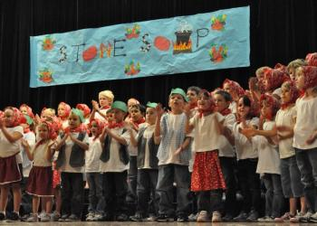 "The chorus sings the overture, ""Stone Soup."""