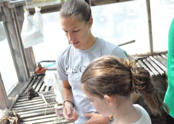 LECOM student Katie Rorer helps Delaney Dowdell, 11, get seeds ready to dry.