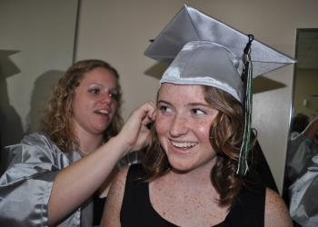 Breanna Howell, behind, helps Emily Wray pin on her cap.