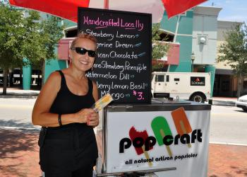 Donna Tortorice, co-owner of Pop Craft, poses out by her cart Monday, August 1 on the sidewalk across the street from Hollywood 20.