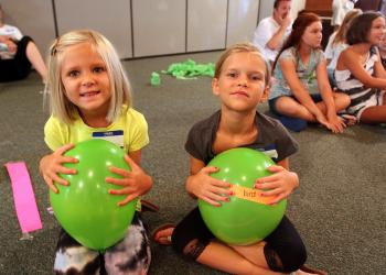 Ava, 4 ½, and Chloe, 6 ½, Tesinksy hold onto green ballons Monday, August 8 during vacation bible school at Siesta Key Chapel.