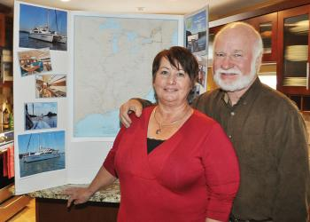 Jean and Ron Schwied stand in their kitchen in front of a map of the route they will be taking. Their home is rented out, and they are ready to take off.