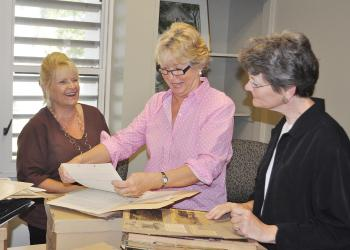 Jane Buckman, Carol Weiss and Winnie Nelon look through the archives.