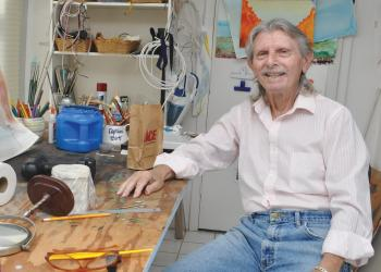 I. Bert Spiegel sits in his studio, located on the lanai, where he paints and conducts small repairs.