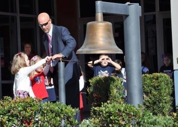 Principal Jim Mennes assisted students with ringing the Freedom Bell in the school courtyard at Freedom Elementary School.