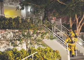 Sarasota County firefighters rush into a high-rise building on Siesta Key to expel smoke that lingered from a fire Dec. 9.