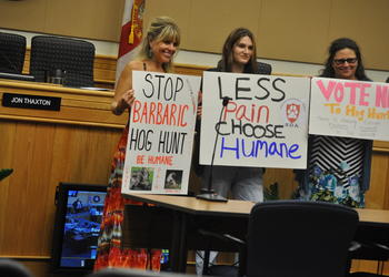 Opponents of the Deer Prairie Creek Preserve hog hunt brought signs to a July 10 Sarasota County Commission meeting.