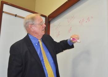 Town labor attorney W. Reynolds Allen calculates the impact of a wage reduction versus a deduction from wages during Thursday's contract negotiations.
