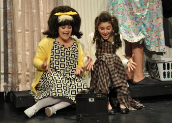 Tracy Turnblad and her best friend Penny Pingleton, played by Gabby Maraia and Julia Bellanger, watch television.