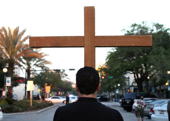 Chris Wood, the youth minister at Church of the Redeemer, carries the cross during the 13th annual Good Friday Morning Stations of the Cross walk.