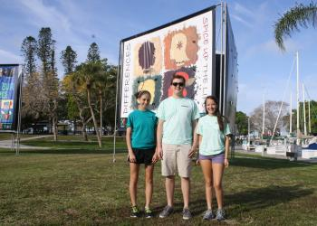Colleen Manning, Matt Battles and Chelsea Meric in front of one of 39 billboard-sized pieces of artwork promoting a vibrant and inclusive community for every person. Mallory Gnaegy