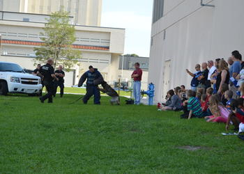 "Children watch closely as Officer Tim Bain and canine partner ""Kuda"" show how a K-9 takes down a suspect."