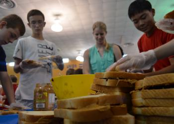 Eight graders Bart Hillerich, Eric Mc Kinnon, senior and table captain Jenny Mooney and eight grader Phillip Tran make sandwiches to break the Guinness World Record.