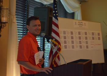 YPG Chairman Sam Davidson reminds golfers to bid on silent auction items before it closes.