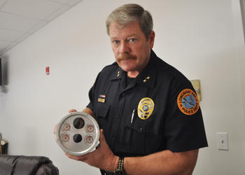 Longboat Key Police Chief Pete Cumming holds one of the cameras, which have a color camera, infrared camera and four illuminators.