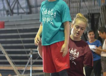Camp counselor Alison Krizen helps camper Sarah Windom, 10, balance on the globes.