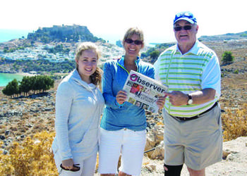 GREECE LIGHTNING. Ashley Munroe, Suzanne Munroe and George Bradicich took their Sarasota Observer along on a trip to Rhodes, Greece, recently. The acropolis of Lindos sits behind them.