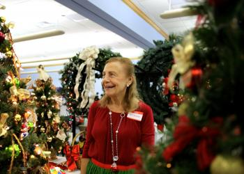 Vivian Leahy laughs as she turns on the lights for one of the decorated trees.