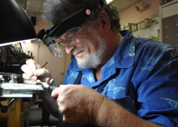 Photo by Pam Eubanks. Stephen Powell, owner of Jewelry by Cole, crafts jewelry at his store on St. Armands Circle.