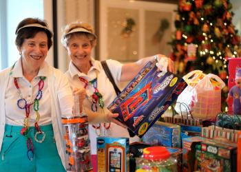 Hannah Weinberg and Anita Cohen add gifts they brought for children in need to a table full of donated toys.