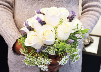 A wedding bouquet at Beneva Flowers made of trendy lilac, Queen Anne's lace, white roses and greenery.