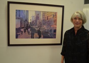 "Kris Parins in front of her watercolor entitled ""Empire State."""