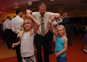 Brad Gemme twirls his daughters, Madilyn, let, and Chelsea, right.