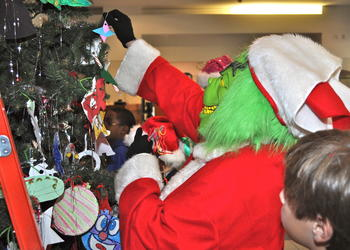 The Grinch (Ann White) decorates the Christmas tree at the Sarasota Courthouse.