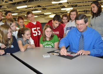 Students at McIntosh Middle School watch as Principal David Jones shows them a slight of hand trick.