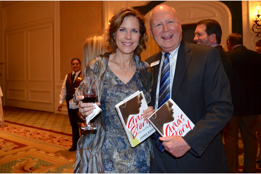 "Jill Levine and Scott Anderson hold up the copies of Jenna Bush Hager's book ""Ana's Story: A Journey of Hope"" that they received at the event."
