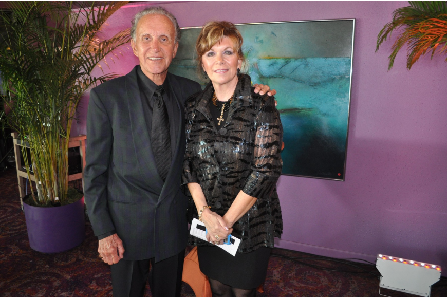 Darrell and Lesley Huntley pose in front of the painting they donated.