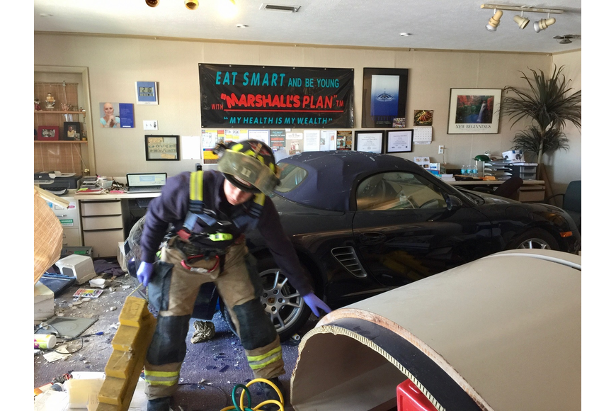 Sarasota County emergency personnel begin picking through the rubble after a car crashed through the front of a south Sarasota business last Thursday.