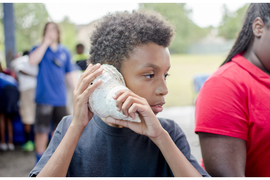 Tishod listens to a sea shell during the Mote presentation that followed the ribbon cutting.