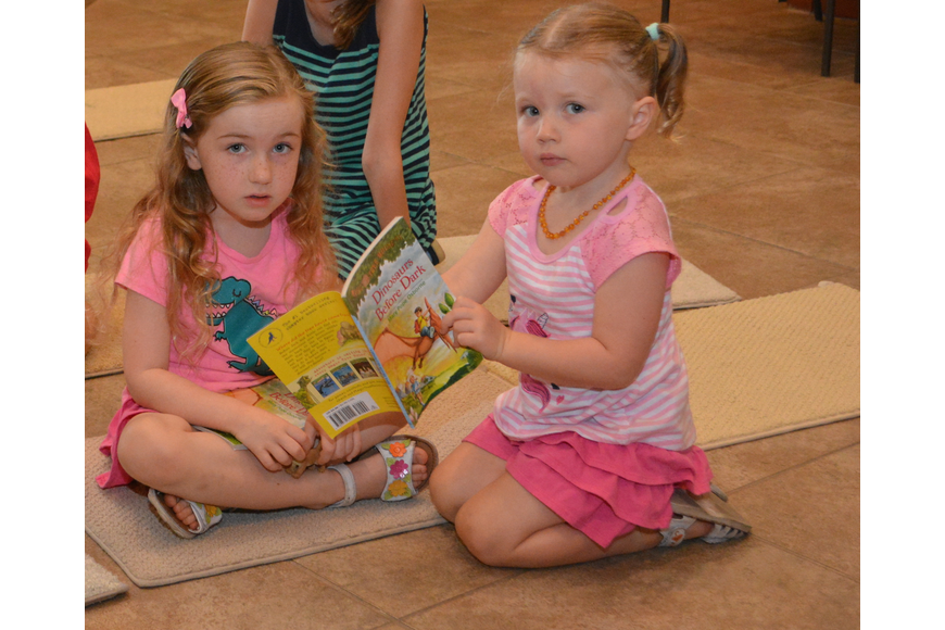 Mya, 5, and Ayla, 2, Kroot of Bradenton check out a book before the STAR series event began at the Sarasota Polo Club.