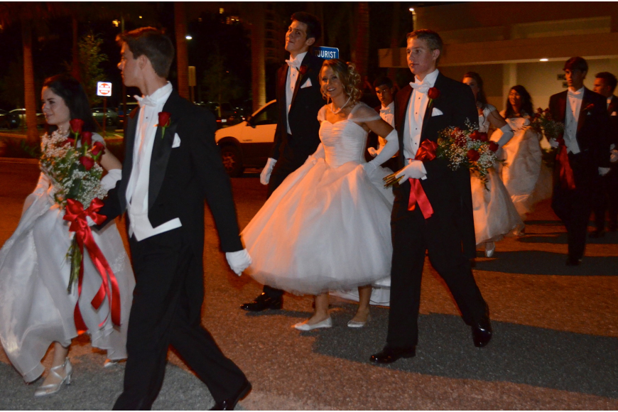 The debutantes and their escorts make their way to the auditorium.