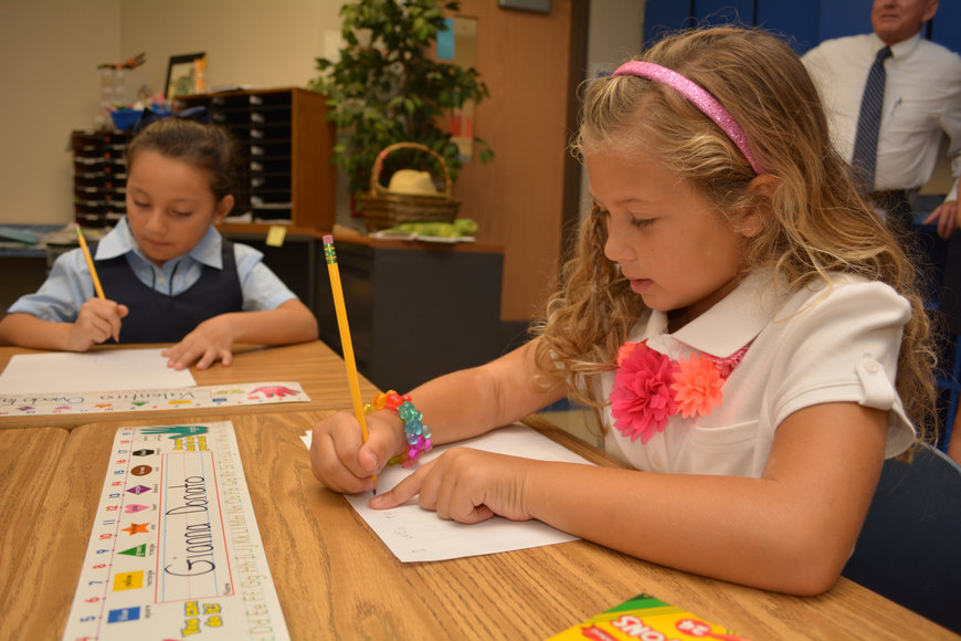 Gianna Donato, in white, gets busy in her new first-grade class.