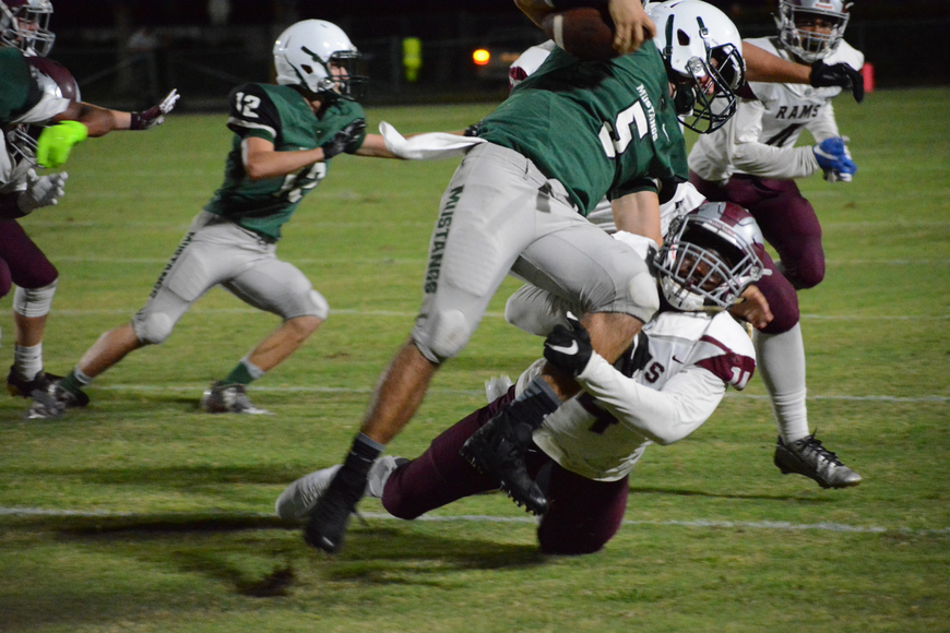 Lakewood Ranch quarterback Justin Curtis runs over a defender.